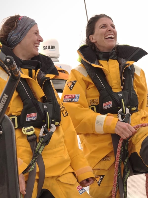 Two ladies laughing on a Clipper yacht while wearing yellow sailing gear